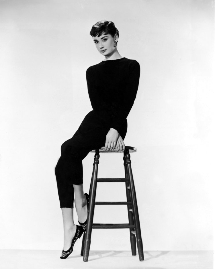 Audrey Hepburn on a stool, exhibiting poise